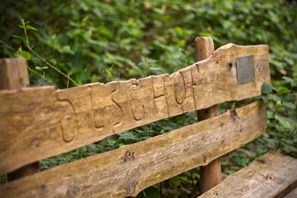 Jede Holzbank neben einer Skulptur besitzt eine individuelle Inschrift.