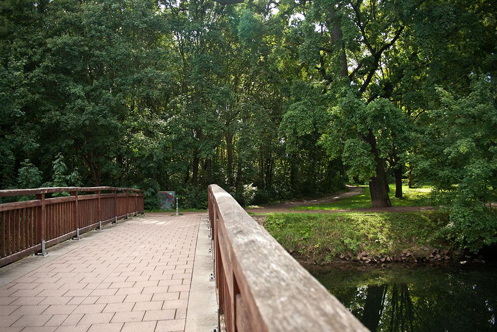 Hinter der Kirche liegt der Kirchteich, übder den zwei Brücken führen.